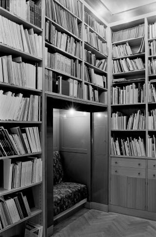 Auf diesem s/w-Foto sind eine Leseecke und mehrere Bücherregale zu sehen